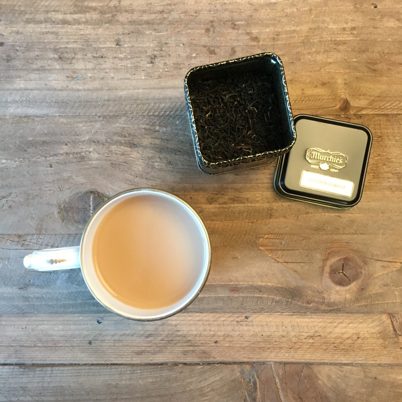 Cup of tea and loose leaf tea on a wooden table